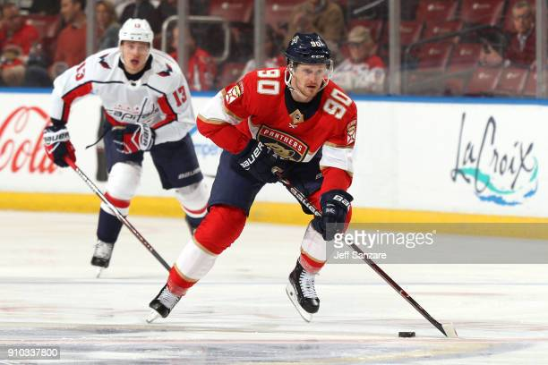 Jared McCann of the Florida Panthers skates with the puck against Jakub Vrana of the Washington Capitals at the BBT Center on January 25 2018 in...