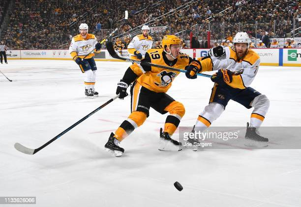 Jared McCann of the Pittsburgh Penguins battles against Yannick Weber of the Nashville Predators at PPG Paints Arena on March 29 2019 in Pittsburgh...