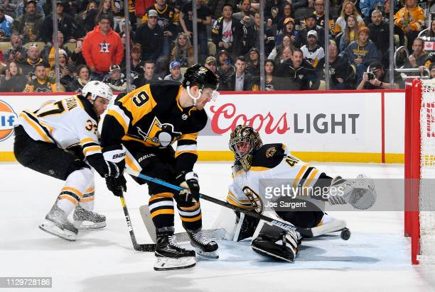 Jared McCann of the Pittsburgh Penguins scores past Jaroslav Halak of the Boston Bruins at PPG Paints Arena on March 10 2019 in Pittsburgh...