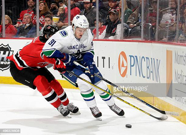 Jared McCann of the Vancouver Canucks battles for control of the puck against the New Jersey Devils during the first period at the Prudential Center...