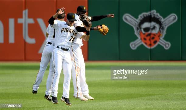 Jared Oliva of the Pittsburgh Pirates celebrates with Bryan Reynolds and Gregory Polanco after defeating the Chicago Cubs 7-0 at PNC Park on...