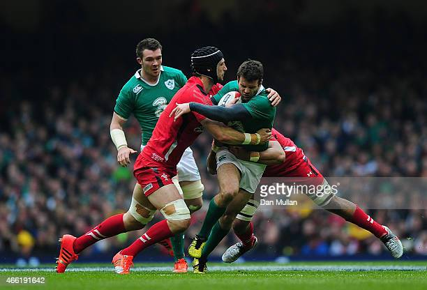 Jared Payne of Ireland is tackled by Luke Charteris and Taulupe Faletau of Wales during the RBS Six Nations match between Wales and Ireland at...
