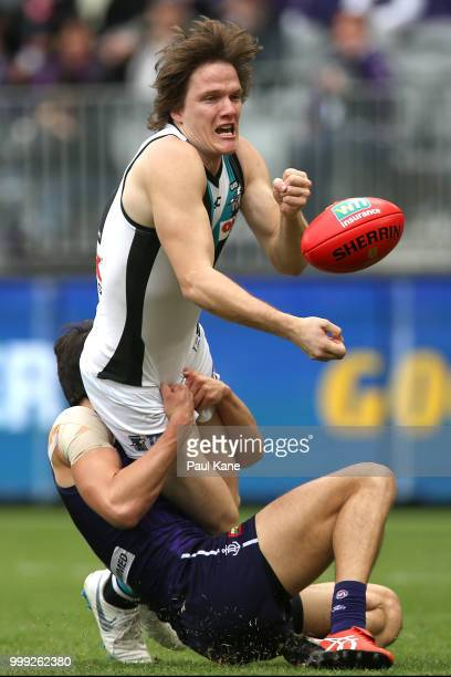 Jared Polec of the Power gets his handball away while being tackled by Andrew Brayshaw of the Dockers during the round 17 AFL match between the...