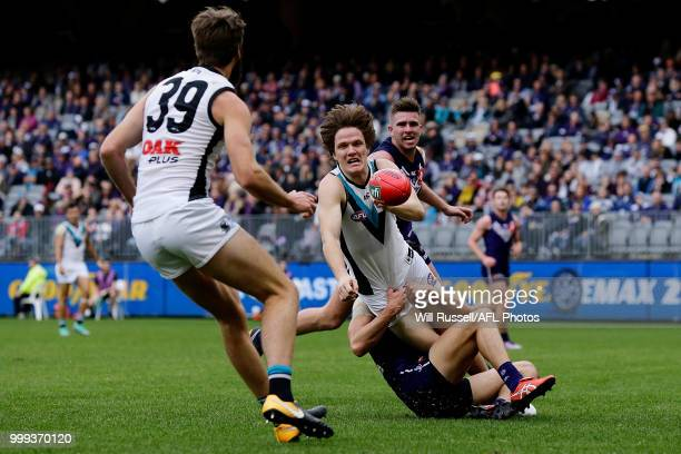 Jared Polec of the Power handpasses the ball under pressure from Adam Cerra of the Dockers during the round 17 AFL match between the Fremantle...
