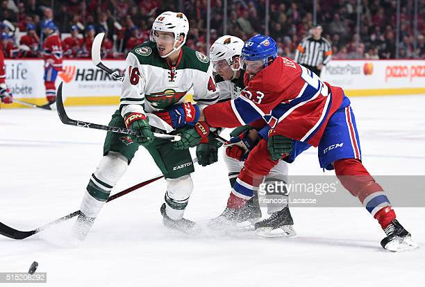 Jared Spurgeon and Zach Parise of the Minnesota Wild defend against Lucas Lessio the Montreal Canadiens in the NHL game at the Bell Centre on March...