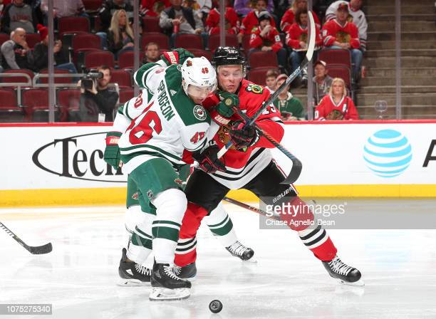 Jared Spurgeon of the Minnesota Wild and Jonathan Toews of the Chicago Blackhawks battle for the puck in the second period at the United Center on...