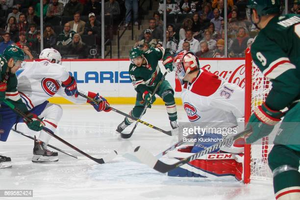 Jared Spurgeon of the Minnesota Wild scores a goal with Karl Alzner and goalie Carey Price of the Montreal Canadiens defending during the game at the...