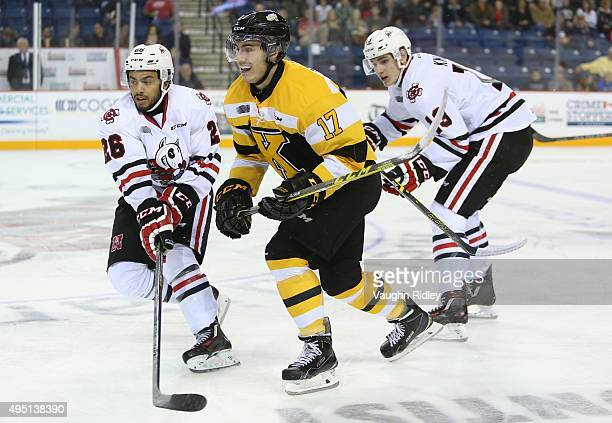 Jared Steege of the Kingston Frontenacs is checked by Josh HoSang and Graham Knott of the Niagara IceDogs during an OHL game at the Meridian Centre...