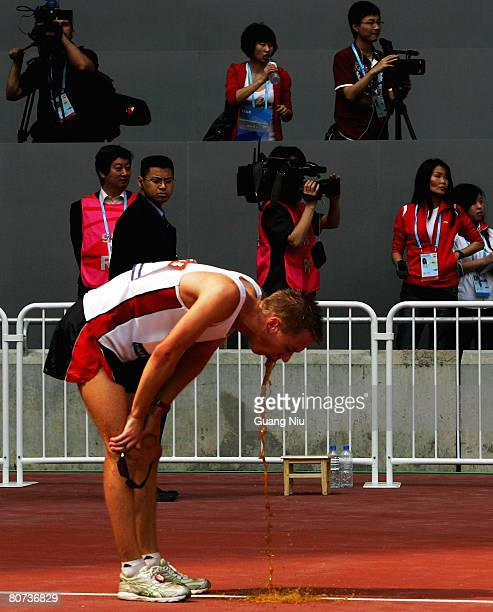 Jared Tallent of Australia vomits on the track after his victory in the men's 20 km walk race during the 2008 BBMG IAAF Race Walking Challenge at the...