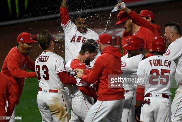 Jared Walsh of the Los Angeles Angels is mobbed by his teammates as he celebrates his game winning three run home run in the ninth inning against...