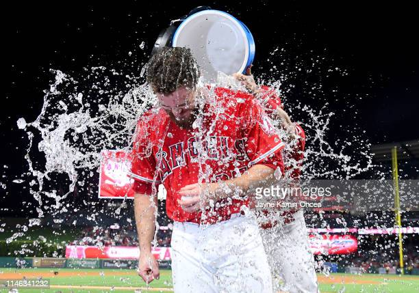Jared Walsh of the Los Angeles Angels of Anaheim gets a celebratory ice water bath from Mike Trout of the Los Angeles Angels of Anaheim after hitting...