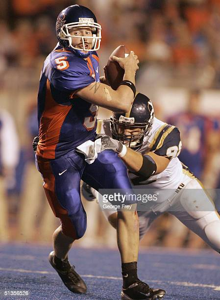 Jared Zabransky quarterback of Boise State scrambles out of a tackle by John Denney of BYU September 24 2004 at Broncos Stadium in Boise Idaho BSU...