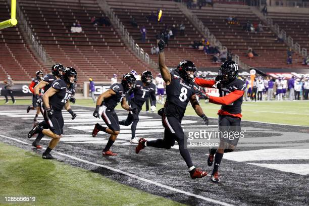 Jarell White of the Cincinnati Bearcats celebrates with teammates after returning an interception 26 yards for a touchdown against the East Carolina...