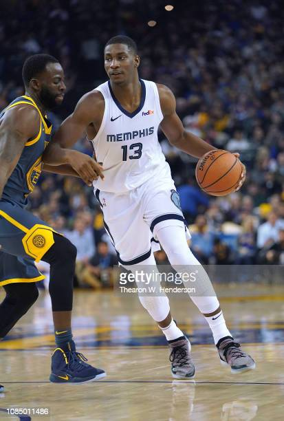 Jaren Jackson Jr #13 of the Memphis Grizzlies dribbles the ball while guarded by Draymond Green of the Golden State Warriors during an NBA game at...