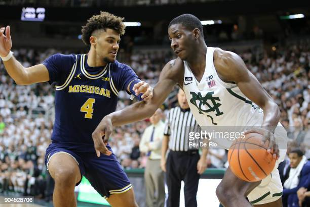 Jaren Jackson Jr #2 of the Michigan State Spartans drives to the basket while defended by Isaiah Livers of the Michigan Wolverines at Breslin Center...