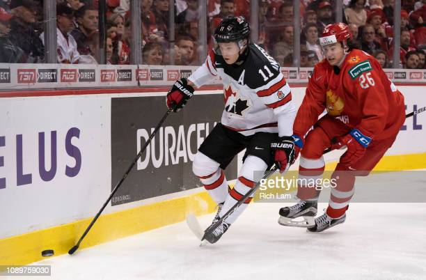 Jaret AndersonDolan of Canada fights off the check of Alexander Romanov of Russia in Group A hockey action of the 2019 IIHF World Junior Championship...