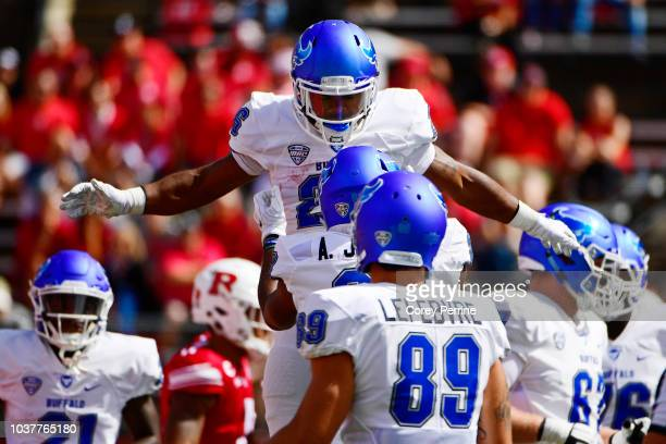 Jaret Patterson of the Buffalo Bulls is lived by teammate Anthony Johnson after scoring a touchdown against the Rutgers Scarlet Knights during the...