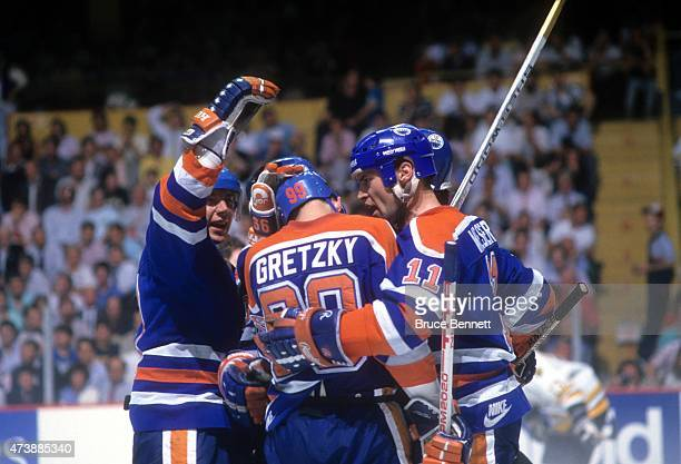 Jari Kurri and Mark Messier of the Edmonton Oilers congratulate teammate Wayne Gretzky after scoring a goal during the 1988 Stanley Cup Finals...