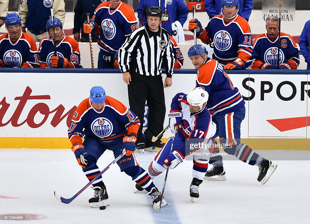 Jari Kurri #17 of the Edmonton Oilers alumni battles for a loose puck with Kris King #17 of the Winnipeg Jets alumni during the 2016 Tim Hortons NHL Heritage Classic alumni game at Investors Group Field on October 22, 2016 in Winnipeg, Canada.