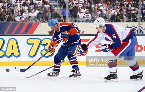 Jari Kurri of the Edmonton Oilers alumni pulls the puck away from Jim Kyte of the Winnipeg Jets alumni during the 2016 Tim Hortons NHL Heritage...