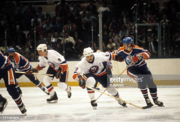 Jari Kurri of the Edmonton Oilers is defended by Bryan Trottier of the New York Islanders during the 1984 Stanley Cup Finals in May 1984 at the...