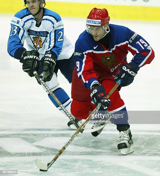 Jari Viuhkola of Finland chases Alexei Yashin of Russia in the teams' Group F qualifier match at the International Ice Hockey Federation World...