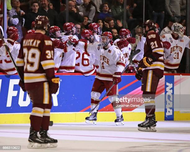 Jarid Lukosevicius of the Denver Pioneers is congratulated by teammates after scoring a hat trick in the second period against the Minnesota-Duluth...