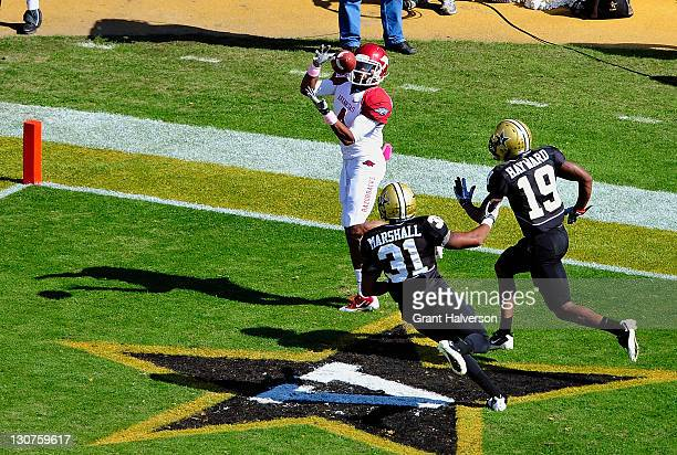 Jarius Wright of the Arkansas Razorbacks makes a touchdown catch against Javon Marshall and Casey Hayward of the Vanderbilt Commodores during play at...