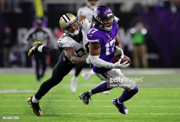 Jarius Wright of the Minnesota Vikings catches the ball over defender PJ Williams of the New Orleans Saints in the fourth quarter of the NFC...