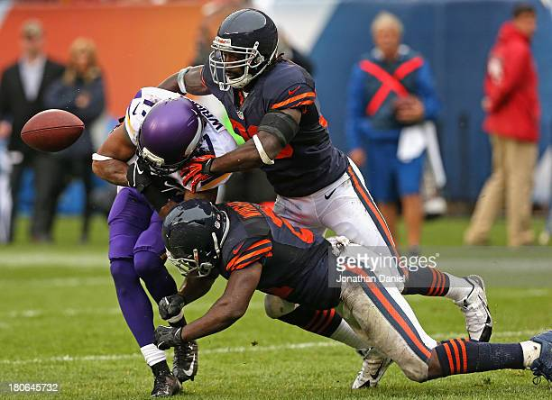 Jarius Wright of the Minnesota Vikings looses control of the ball as he is hit by Charles Tillman and Major Wright of the Chicago Bears at Soldier...