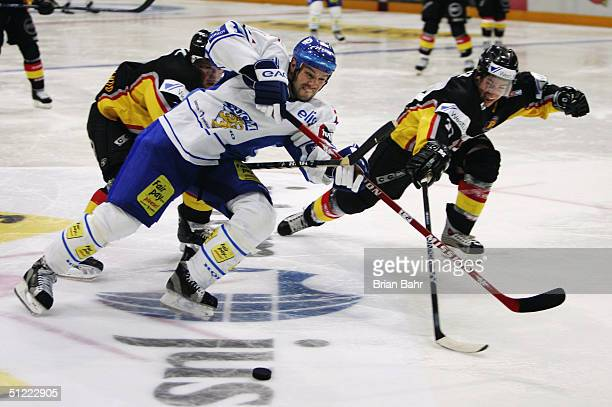 Jarkko Ruuto of Finland struggles to get inside with the puck against Andreas Renz of Germany in the third period during an exhibition game of the...