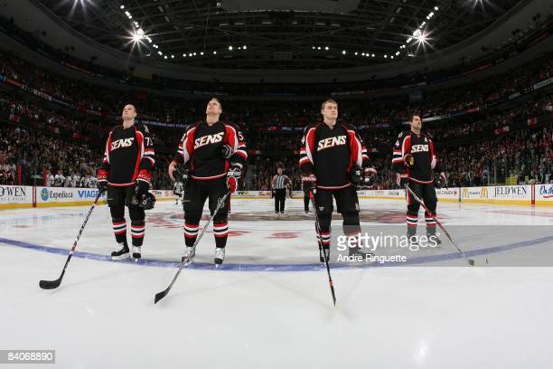 Jarkko Ruutu, Cody Bass, Anton Volchenkov and Chris Phillips of the Ottawa Senators stand at the blue line during the singing of the national anthems...