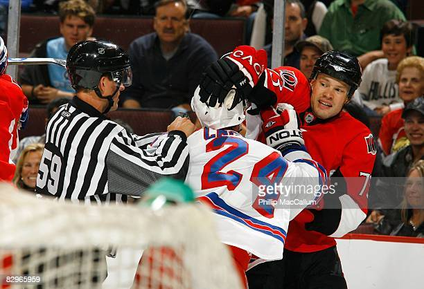 Jarkko Ruutu of the Ottawa Senators and Ryan Callahan of the New York Rangers tussle as NHL Linesman Steve Barton tries to break up the scrum during...