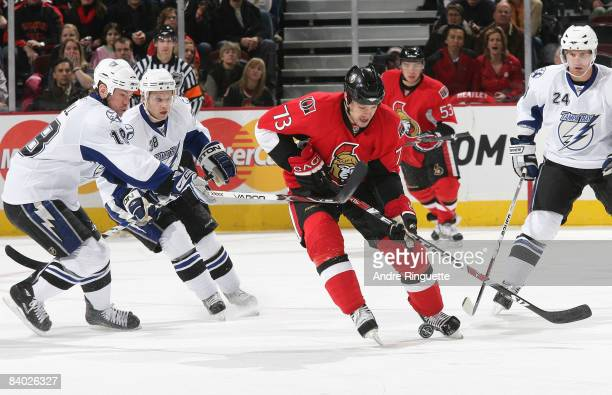 Jarkko Ruutu of the Ottawa Senators stickhandles the puck against Adam Hall Paul Szczechura and Matt Pettinger of the Tampa Bay Lightning at...