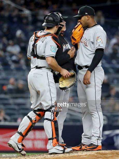 Jarlin Garcia of the Miami Marlins talks with catcher JT Realmuto and Juan Nieves with Giancarlo Stanton of the New York Yankees at bat in the third...