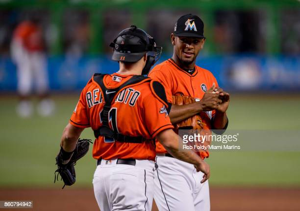Jarlin Garcia of the Miami Marlins talks with JT Realmuto during the game against the New York Mets at Marlins Park on April 16 2017 in Miami Florida