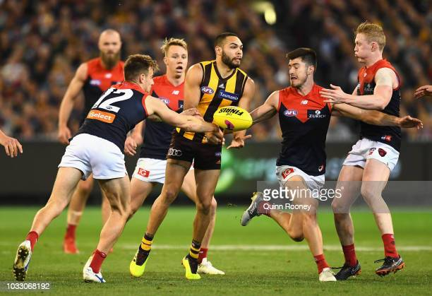 Jarman Impey of the Hawks handballs whilst being tackled by Dom Tyson of the Demons during the AFL Semi Final match between the Hawthorn Hawks and...