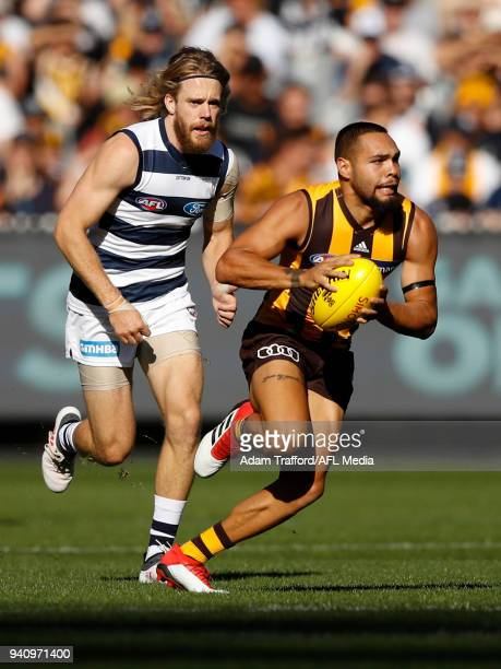 Jarman Impey of the Hawks in action ahead of Cameron Guthrie of the Cats during the 2018 AFL round 02 match between the Geelong Cats and the Hawthorn...