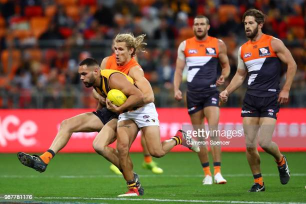 Jarman Impey of the Hawks is tackled during the round 15 AFL match between the Greater Western Sydney Giants and the Hawthorn Hawks at Spotless...