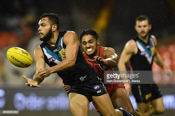 Jarman Impey of the Power handballs under pressure during the round 22 AFL match between the Gold Coast Suns and the Port Adelaide Power at Metricon...