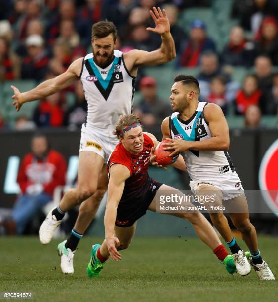 Jarman Impey of the Power is chased by Jayden Hunt of the Demons during the 2017 AFL round 18 match between the Melbourne Demons and the Port...