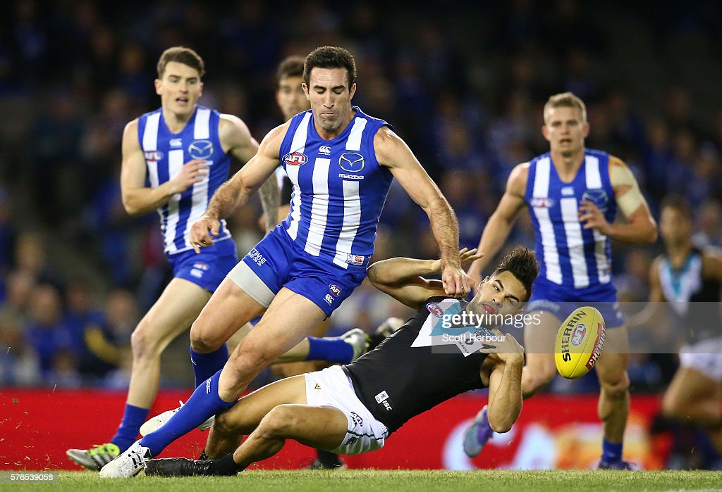 Jarman Impey of the Power is hit in a big tackle by Michael Firrito of the Kangaroos during the round 17 AFL match between the North Melbourne Kangaroos and the Port Adelaide Power at Etihad Stadium on July 16, 2016 in Melbourne, Australia.