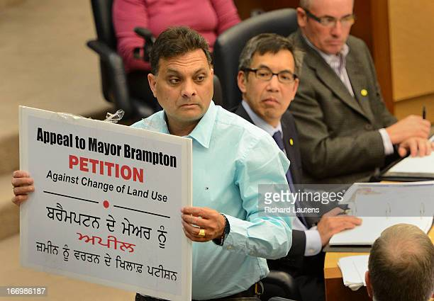 Jarnail Singh holds up a sign to the audience as he delivers a petition to Council against the new development. Brampton council votes Thursday...