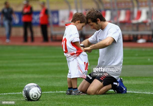 Jarno Trulli of Italy and Lotus is pictured with his son ahead the football charity match between the Monaco star team and the team of formula one...