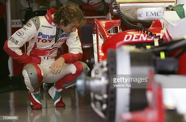 Jarno Trulli of Italy and Toyota looks over his car in the garage during the first practice session for the Japanese Formula One Grand Prix at the...