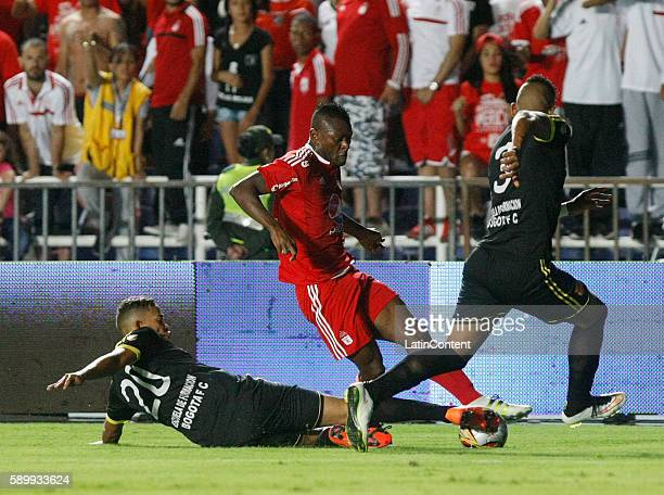 Jarol Martinez of America de Cali fights for the ball with Oaldier Morales and Jeison Quinonez of Bogota during a match between America de Cali and...