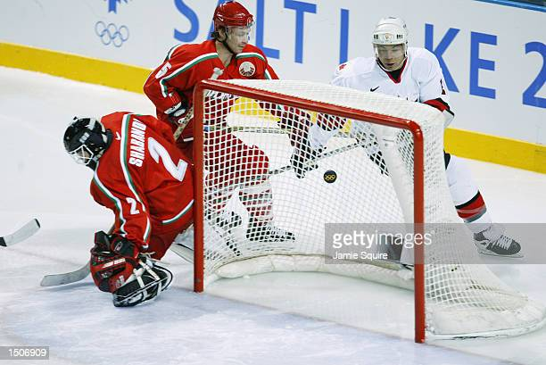 Jarome Iginla of Canada watches as his shot gets past goaltender Sergei Shabanov as he is followed by defenseman Oleg Romanov during the semifinals...