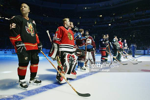 Jarome Iginla of the Calgary Flames and Jocelyn Thibault of the Chicago Blackhawks stand with the rest of the Western Conference team during...