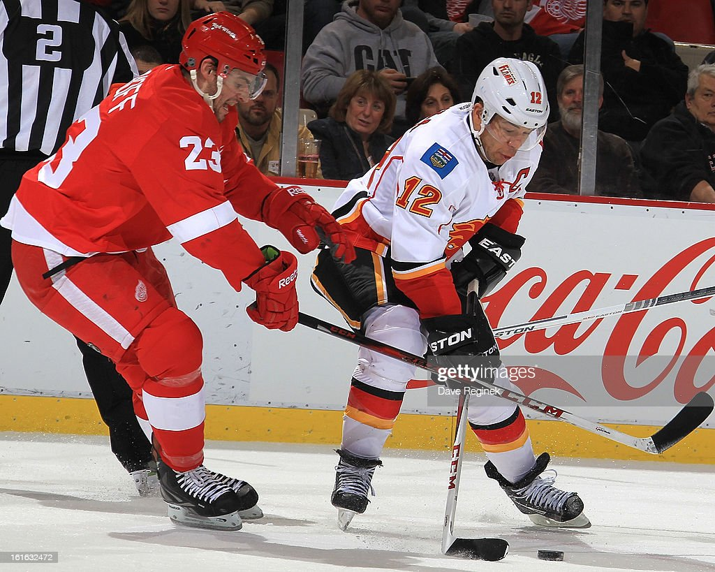 Jarome Iginla #12 of the Calgary Flames battles for the puck with Brian Lashoff #23 of the Detroit Red Wings during an NHL game at Joe Louis Arena on February 5, 2013 in Detroit, Michigan. Calgary defeated Detroit 4-1