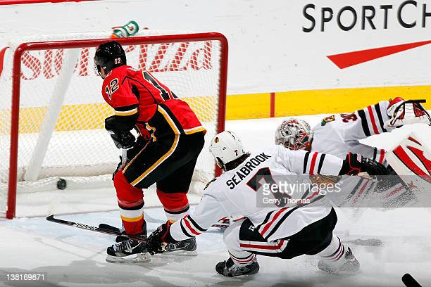 Jarome Iginla of the Calgary Flames scores a goal against an outstretched Ray Emery and Brent Seabrook of the Chicago Blackhawks on February 3 2012...
